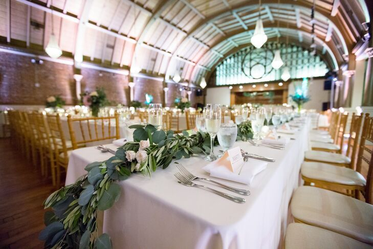 """For the reception, Alexandra and Walter continued the upscale bohemian theme: """"We had a lot of greenery, dim lighting and natural elements."""" Long, white linen-topped tables were adorned with candles and thick garlands of eucalyptus, which were also prominent in the bridal party bouquets."""