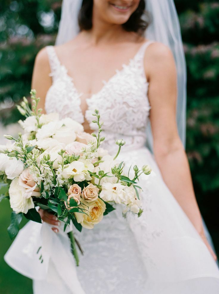 Bride holding green-and-white bouquet