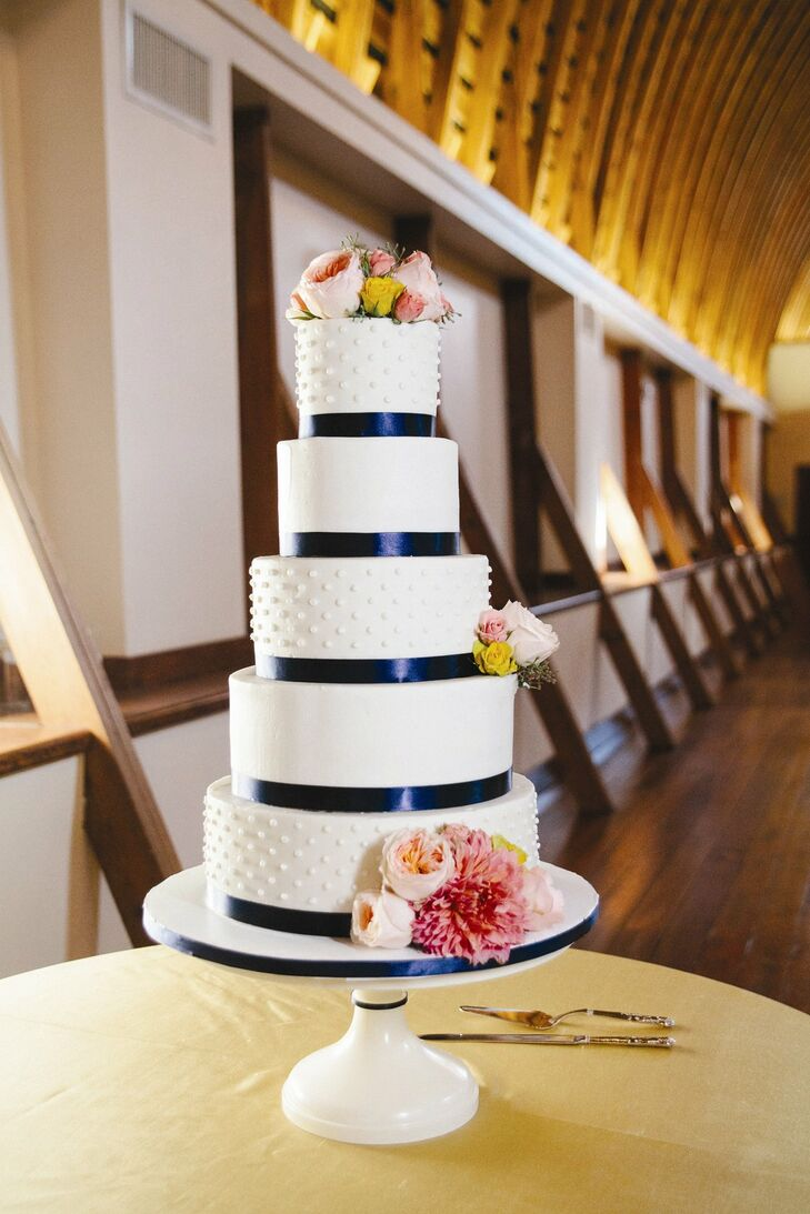Pink flowers, navy ribbon on each tier and white polka dot frosting made the five-tier white cake look preppy and polished.