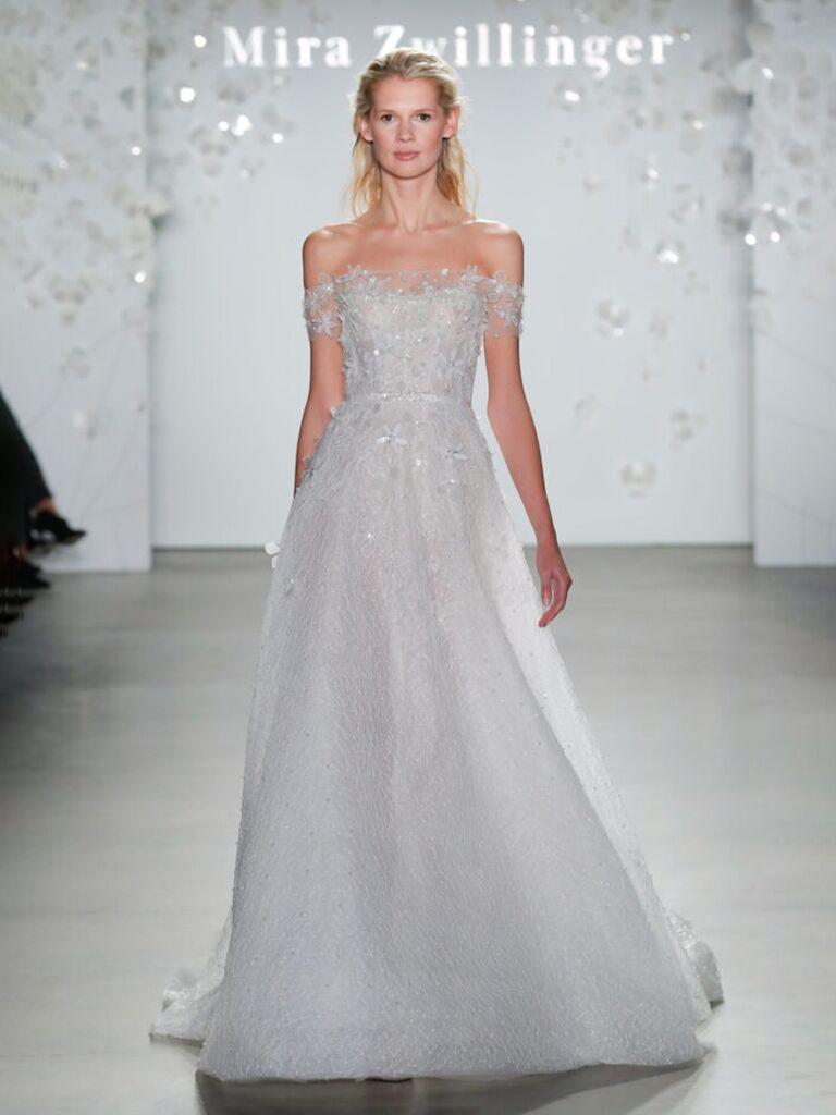 mira zwillinger mặc váy cưới trễ vai màu trắng với ren hoa lấp lánh xếp li váy vải tuyn hoa và nơ sau bằng vải tuyn váy cưới màu trắng đẹp