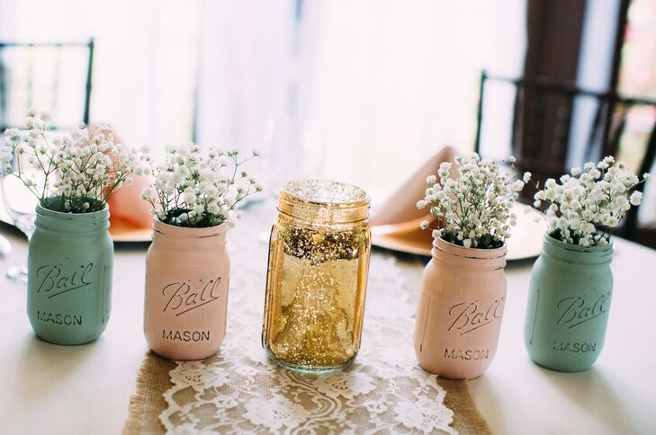 Dining tables at the reception featured burlap and lace table runners. The sweetheart table was decorated with painted blush and mint mason jars filled with baby's breath.