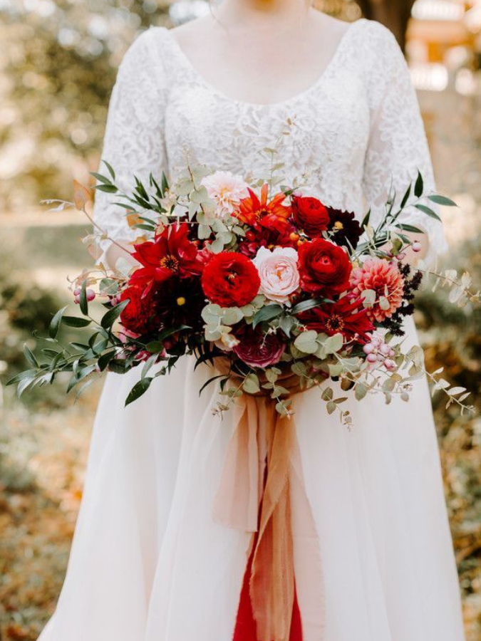 Bride holding bright red bouquet with ribbon