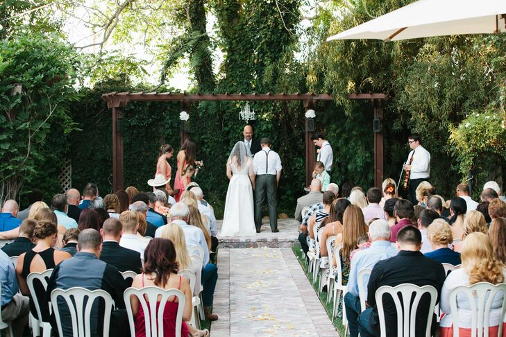 Katie and Dustyn stood at the wooden pergola during their ceremony, which took place outside at Randall House in Bakersfield, California. The landscaped space needed no additional decor past the elegant chandelier that hung above them.