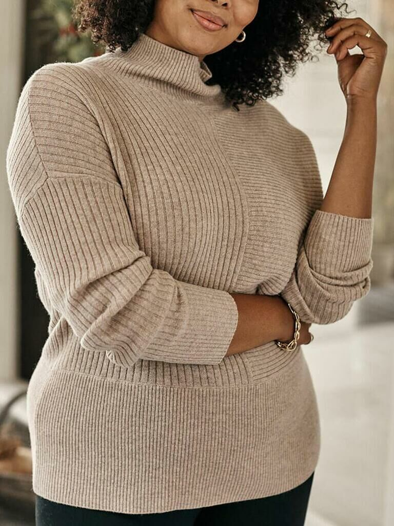 Woman smiling wearing snug cashmere sweater with funnel neck
