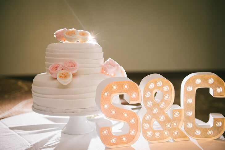 """The cake was perfect for the soft and romantic wedding theme. It was two round tiers covered in ruffles with cute accents of blush and peach garden roses.  A large """"S & C"""" sign for Sharon and Chris lit up the cute display."""
