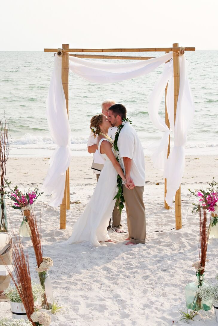 Wanting simpler decor, Nicole and Brad accented their ceremony with a bamboo wedding arch draped in sheer white fabric. For a pop of color, natural fuchsia blooms lined the entrance in colored glass bottles.