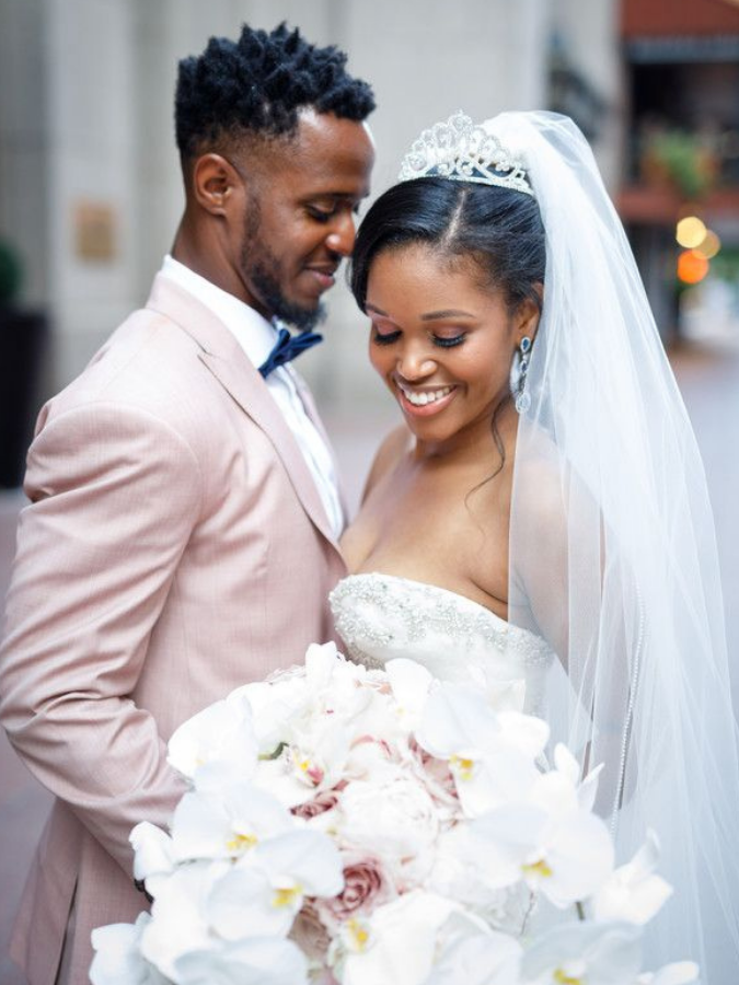 Couple hugging and holding white wedding bouquet