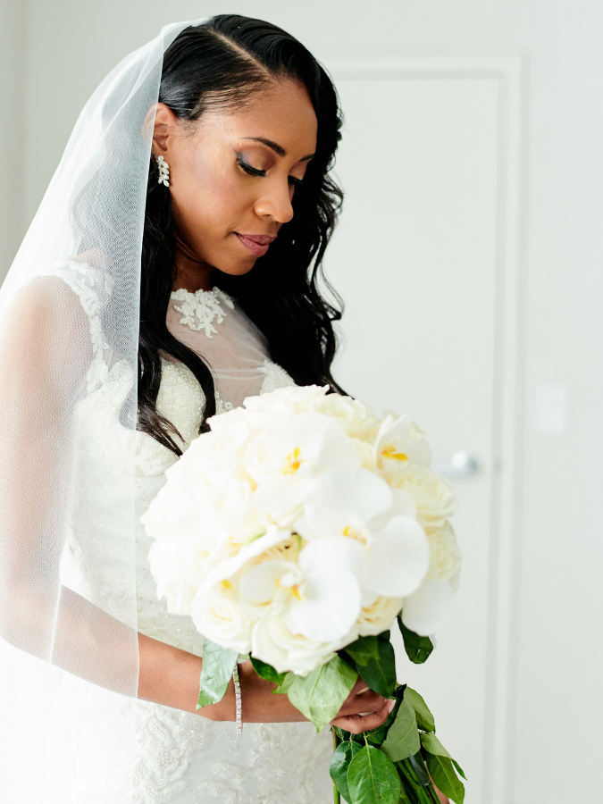 Bride with veil holding white bouquet