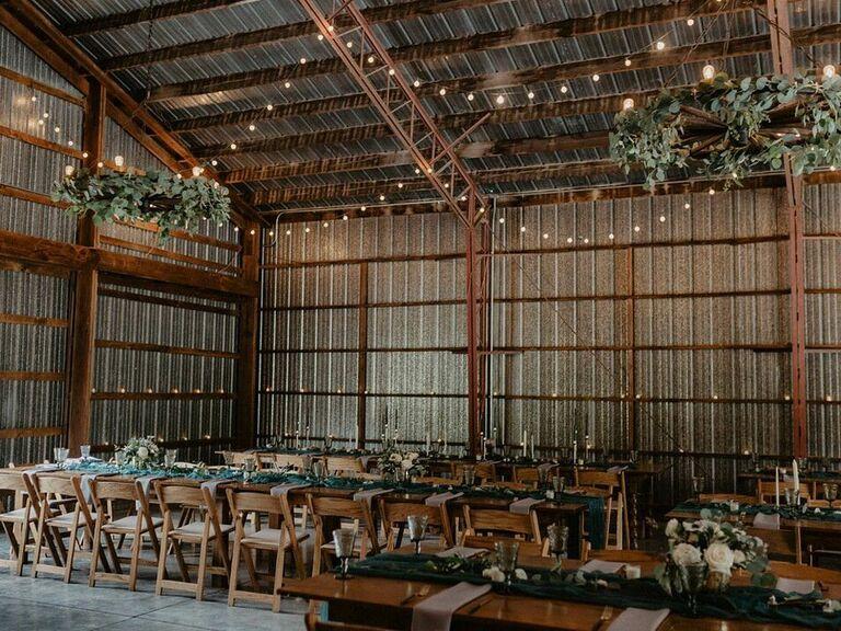 Industrial barn wedding reception with hanging greenery wreaths