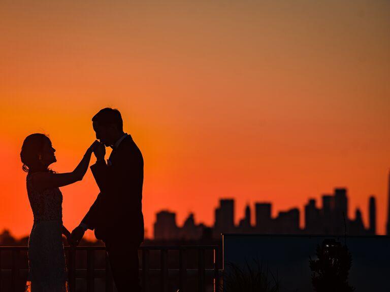 Groom kissing bride's hand silhouette
