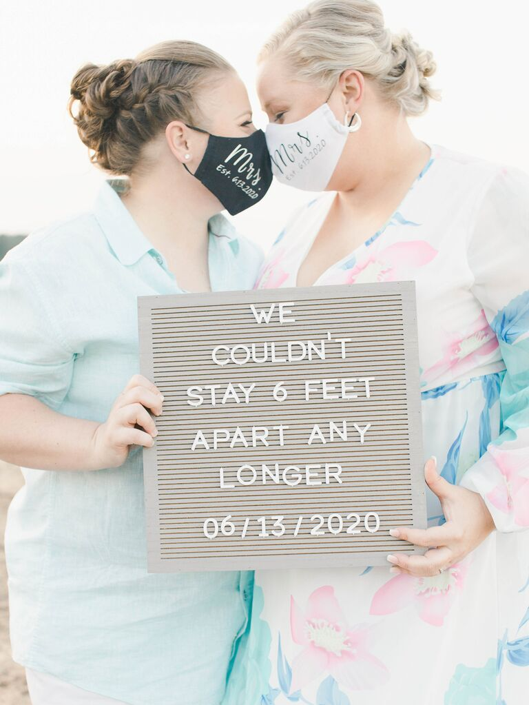 """Same sex brides wearing """"Mrs.""""and """"Mrs."""" wedding face masks with custom letter board"""