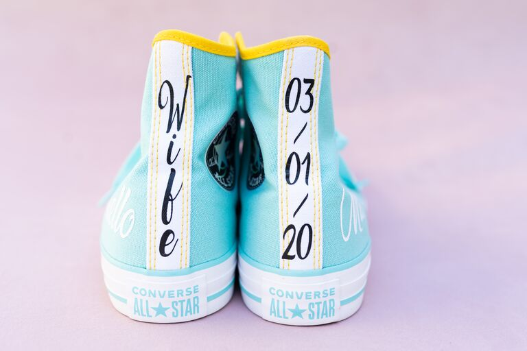 """closeup of bright colorful converse high-top sneakers teal and yellow with """"wife"""" and """"3-01-20"""" wedding date written on the shoes"""