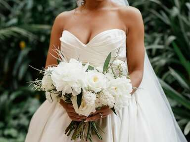 bride in strapless wedding dress holding all-white wedding bouquet