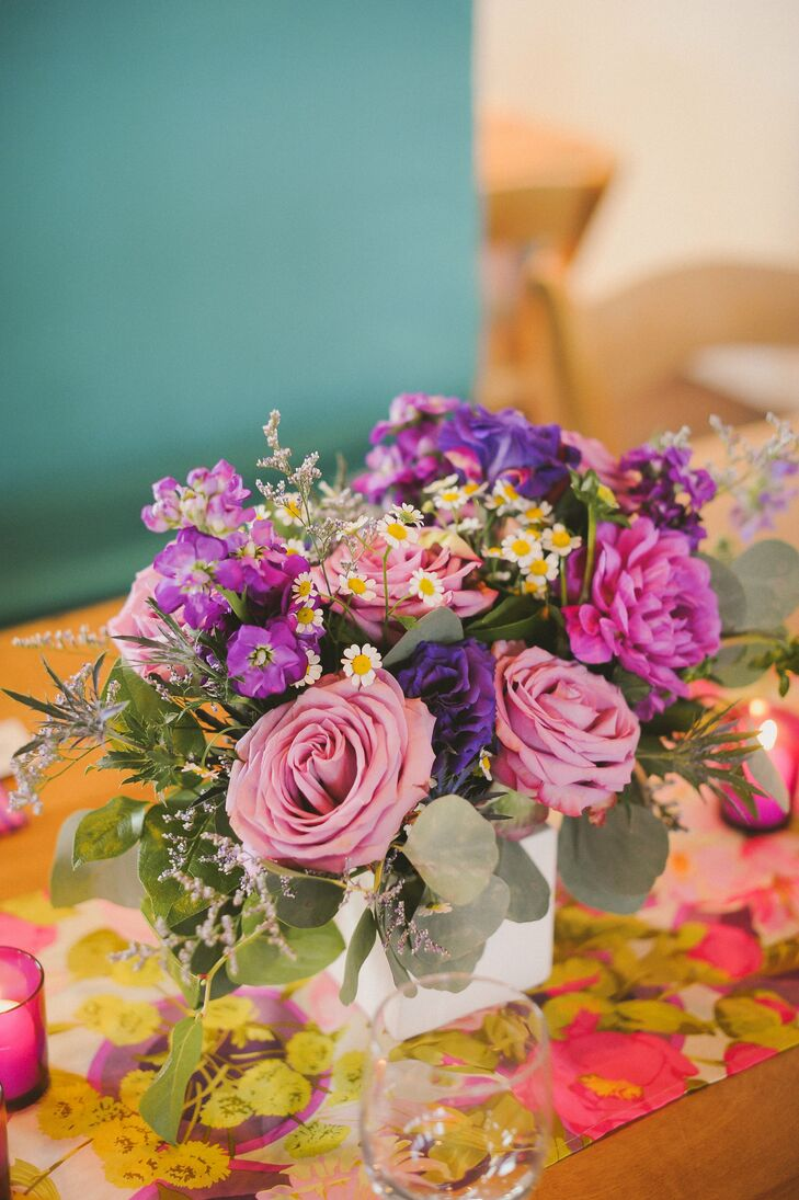 Lavender roses, stock and feverfew in white vases sat on floral runners at the reception.