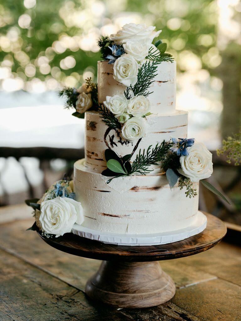 Three-tier rustic wedding cake with birch tree design and fresh flowers