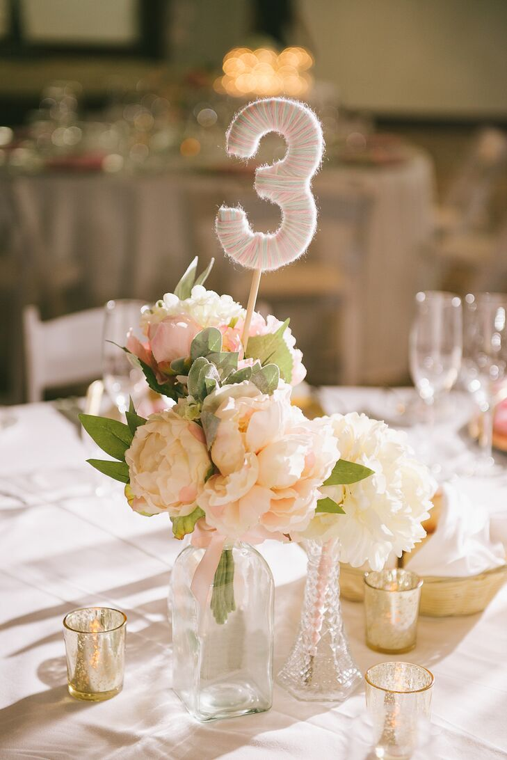 String-wrapped table numbers with silk peonies are super-cute (and make a simple and fun DIY project) for a romantic reception anywhere. Votives in mercury glass were a nice touch to round out the display.