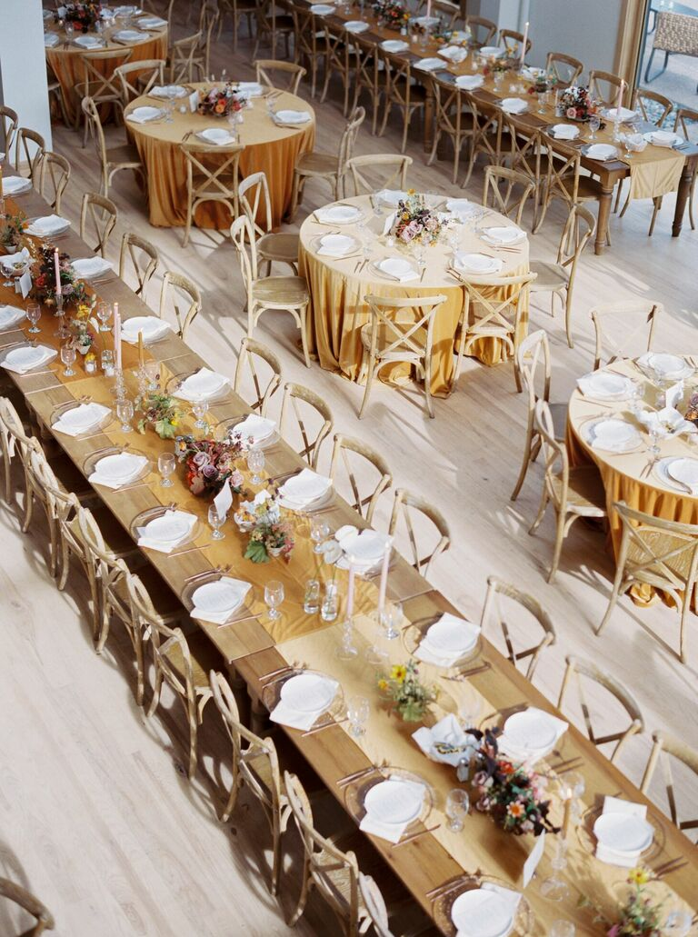 Long farm table with yellow runner and wood cross-back chairs
