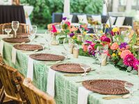Outdoor rehearsal dinner with wicker and floral decor.