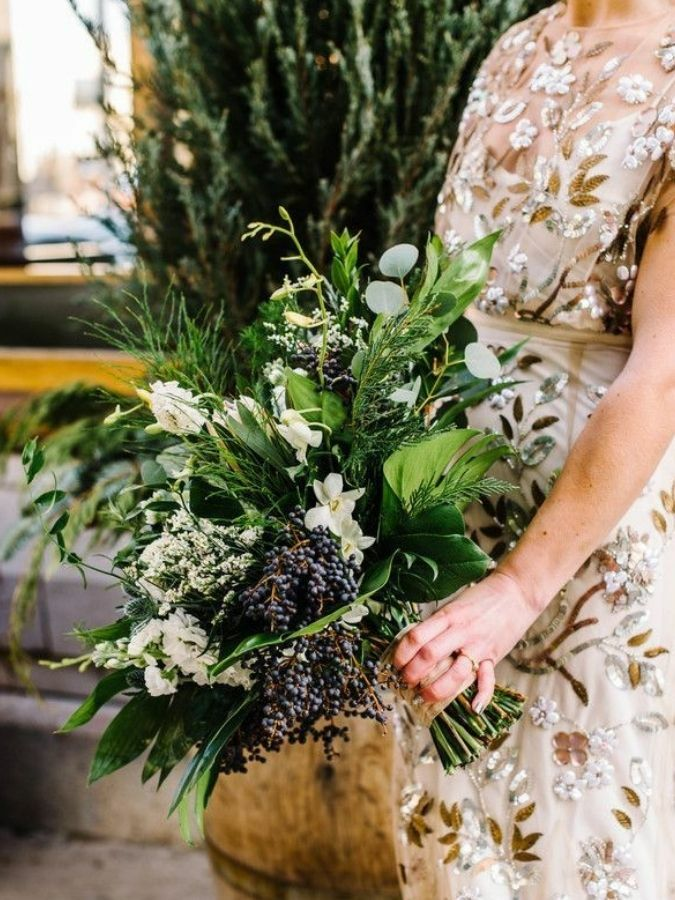 Bride in gold dress holding greenery bouquet