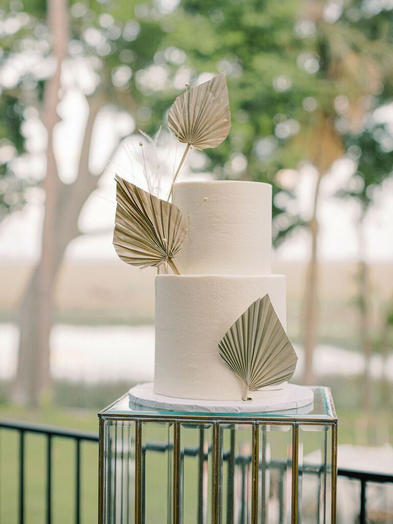Modern two-tier wedding cake with fan-inspired decorations