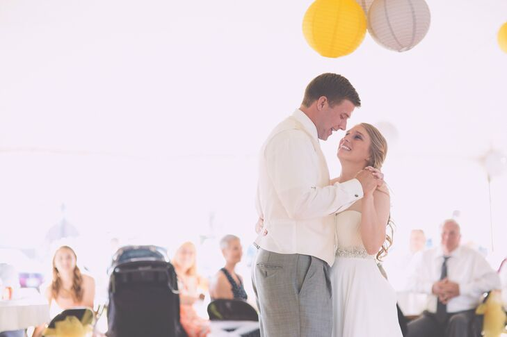 Inside the tent the couple had string lights and hanging yellow and gray lanterns. They wanted to keep the decor simple and light while still incorporating their themes and color palette as much as possible.