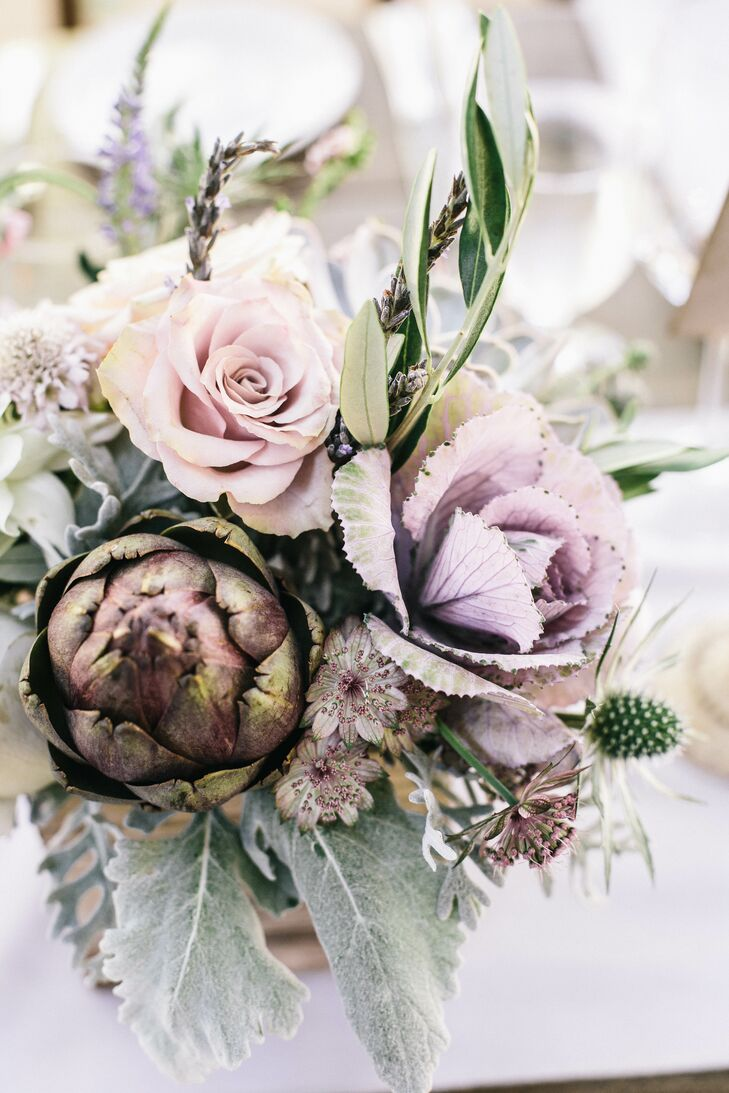 """The couple's florist, Andrea Frenkel, incorporated unusual blooms, like purple artichokes, lavender thistles and pale green succulents, into the centerpieces and bouquets. """"Although the temperature was pushing 100 degrees on the day of our wedding, Andrea made sure we had the freshest, most beautiful blooms,"""" Claire says."""