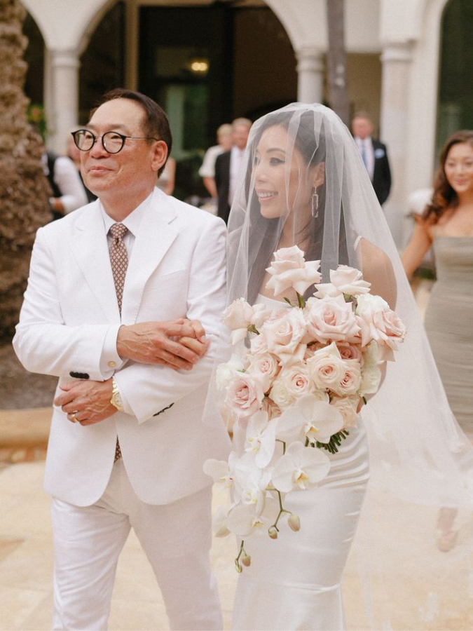 Bride holding bouquet and processing with father