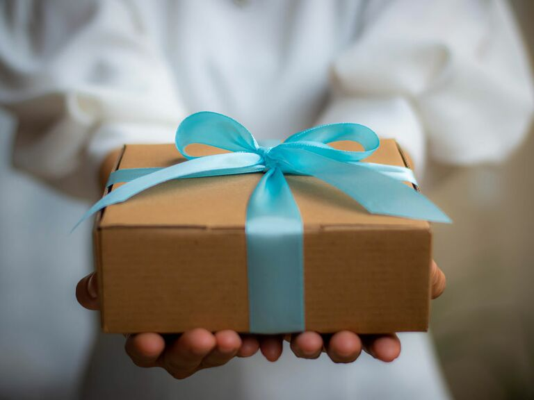 Wedding guest holding gift wrapped in blue bow