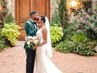 Groom in velvet green tux with bride wearing fit and flare gown with 1920s inspired headband