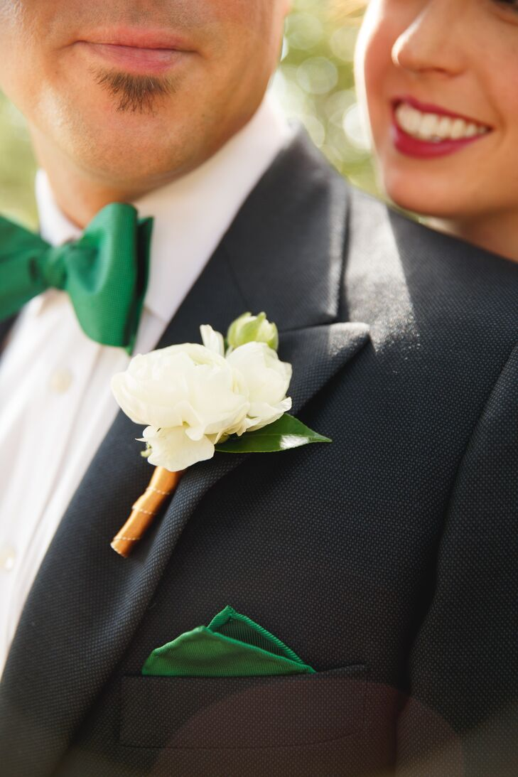 Ben wore a custom suit made by Mario Rojas Custom Tailor in Fort Worth: a Scabal Blue Birdseye two-piece suit and an Egyptian white cotton shirt. He wore a single white ranunculus boutonniere along with a pocket square to match Angela's emerald dress.