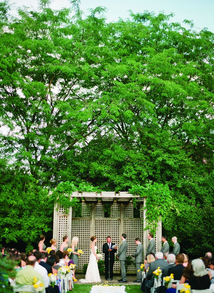 The couple wed outdoors in the garden, where yellow flowers topped chairs.