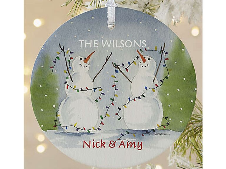 Circle ornament with personalized names and snowmen and Christmas tree graphics