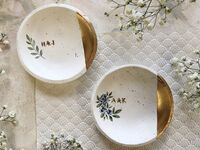 Speckled white dishes with gold detail on side, initials and small greenery and floral design