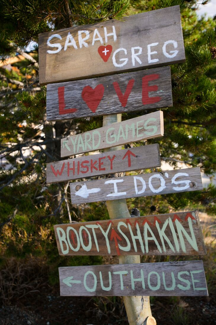 The couple made a rustic wooden wedding sign to point guests in the right direction throughout the day.