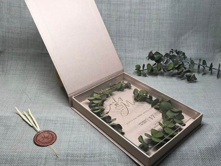 Blush box with clear top and event details in gold type, greenery placed underneath