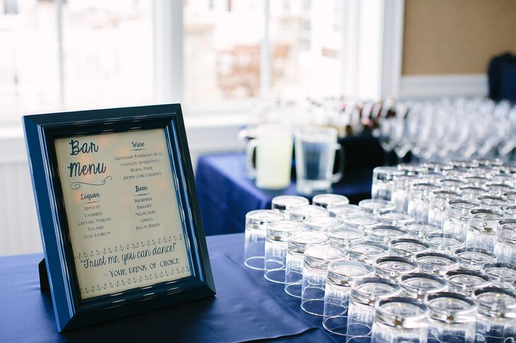 Beer, wine and liquor were served during cocktail hour, which immediately followed the ceremony. A whimsical cream and navy blue sign showed the drink offerings. During cocktail hour, guests could take pictures with props to hang on the couple's homemade photo wall in the venue's hallway.