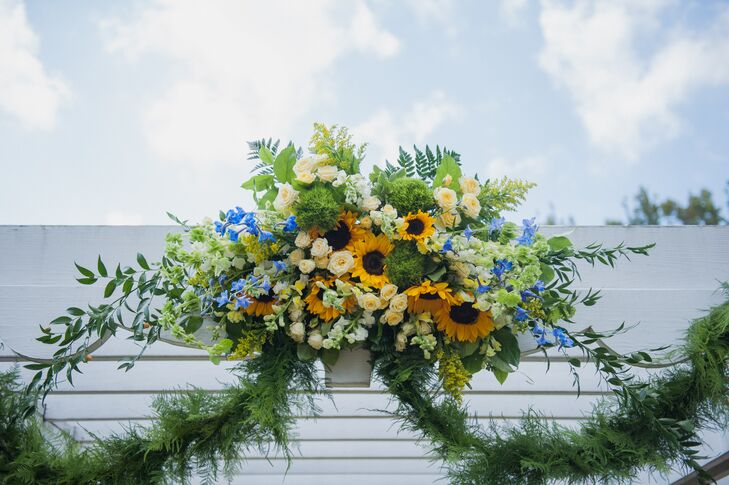 Caitlin and Sean focused on minimal decor, but their white wedding arch was overflowing with florals. Mark Bryan Designs draped the accent in garlands as a lush arrangement of yellow roses, sunflowers, green dianthus, blue orchids and greenery covered the front beam.