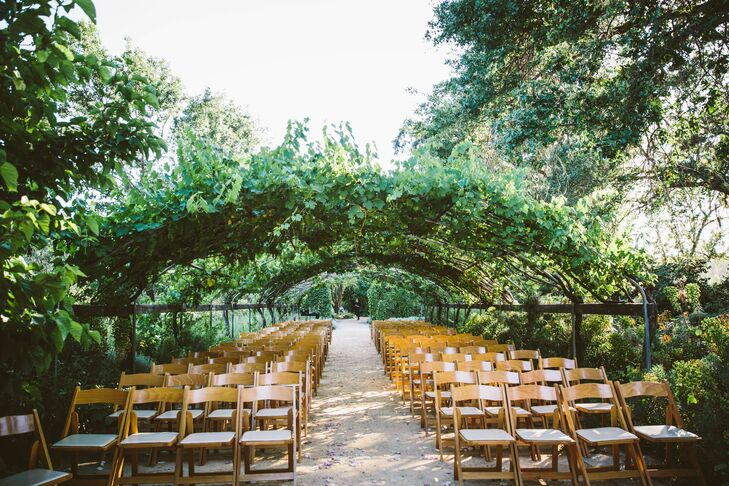 """""""I firmly believe you could host a decor-less wedding in Campovida's mystical gardens and still have one of the most enchanting weddings,"""" Claire says of exchanging vows in the garden under a trellis covered in vines."""