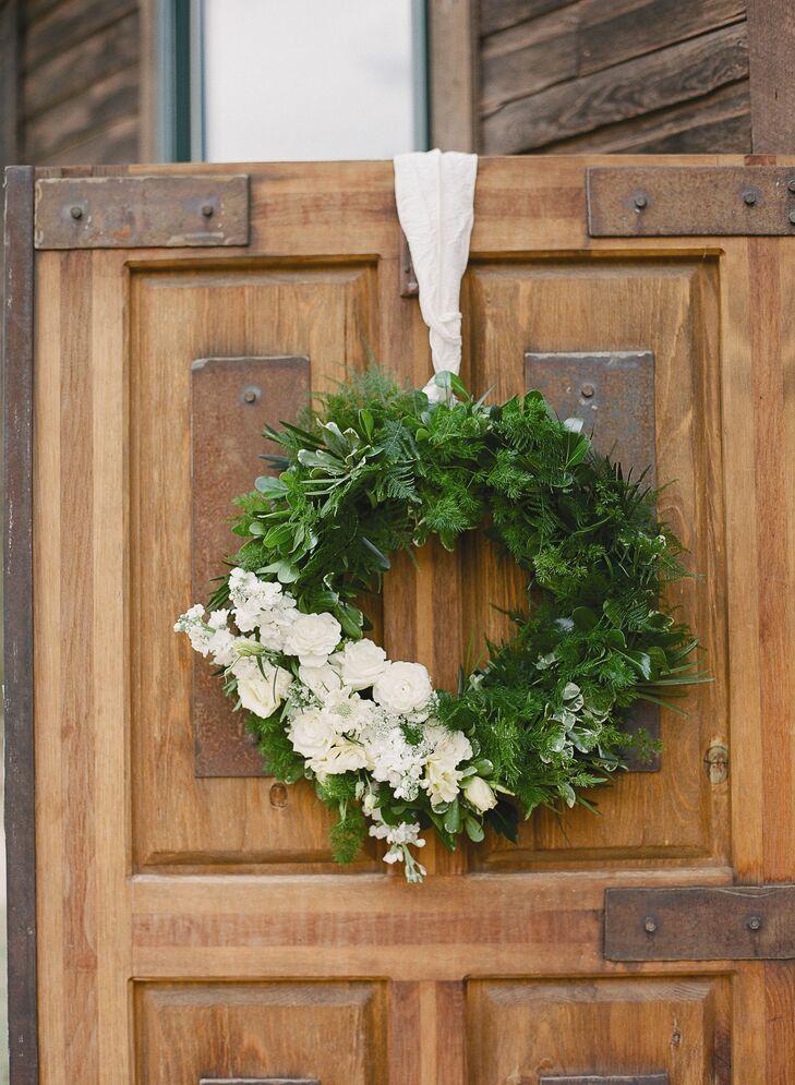 Two green wreaths accented with white flowers hung on the doors of the reception cabin.