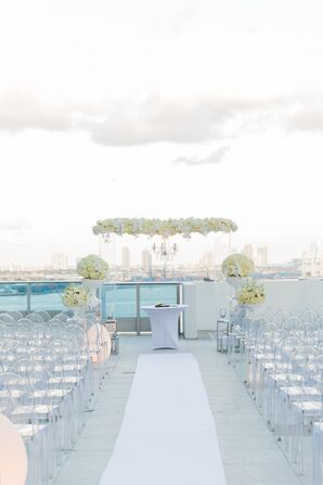 White Floral Wedding Arch and Ghost Chairs