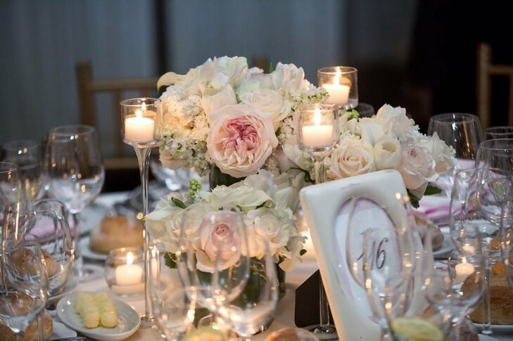 Blush and ivory roses and garden roses with votive candles gave the tables a warm, romantic aesthetic.