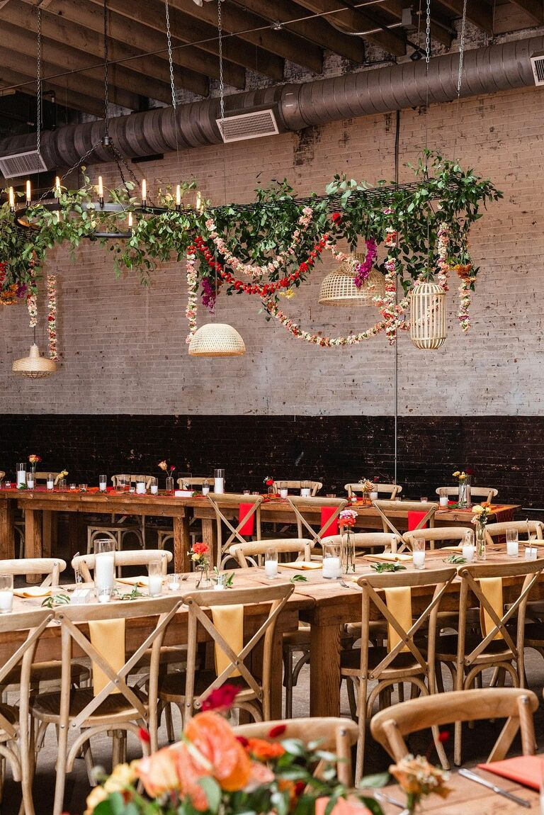 Loft wedding reception with greenery chandelier and cross-back chairs