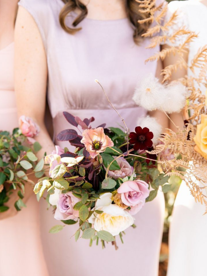 Bridesmaid in purple dress holding bouquet
