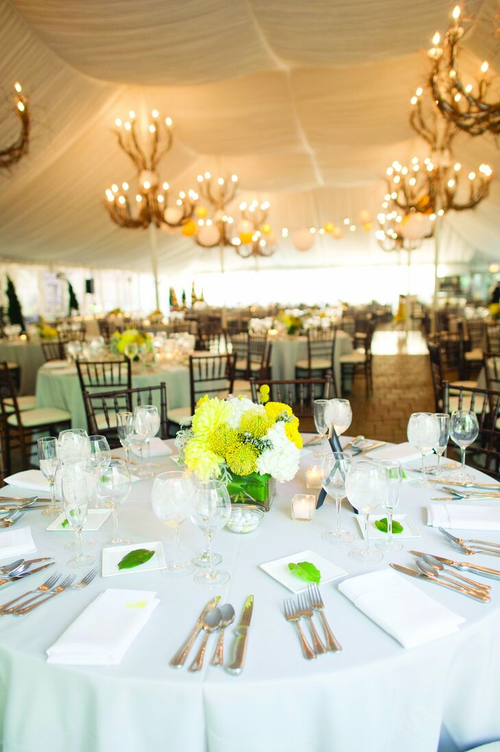 Romantic lighting hung from the tent ceiling, while tables were finished with bright-yellow and white flowers.