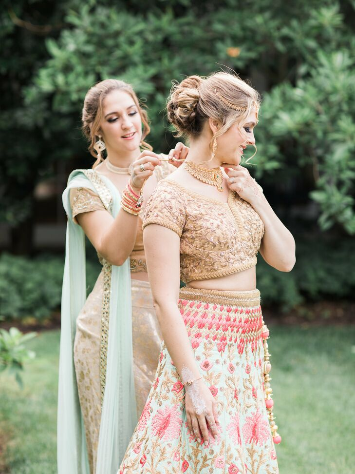 """""""My lehenga consisted of an embroidered gold top was a greenish blue with pink flower accents and a matching scarf,"""" says Arselie, who changed into a purple velvet lehenga for the reception."""