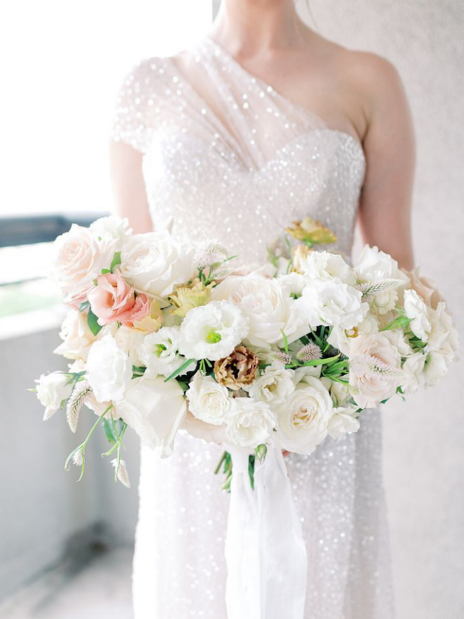Bride in white dress with all-white bouquet