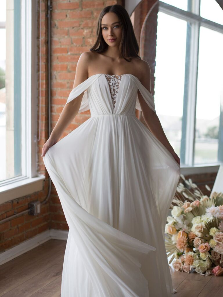 watters white a line wedding dress with v-neckline lace and flowy pleated skirt and off the shoulder sleeves