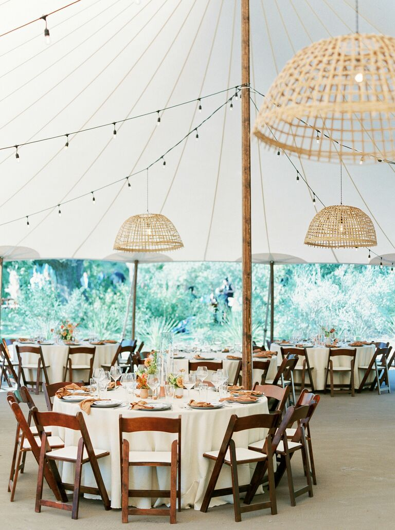 Tented wedding reception with wood folding chairs and woven chandeliers
