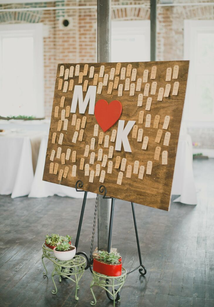 Tiny gift tag escort cards hung from a huge board with handmade initials made by Kristin's father.