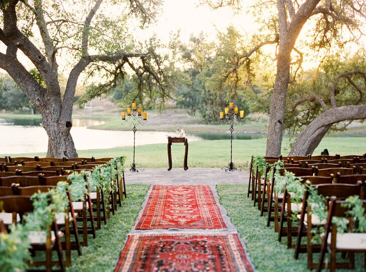 Cody wanted to be married by the water, so they had the ceremony in front of a spring-fed pond on the property. The bright red Turkish rug aisle runner led to the altar, where they got married underneath live oaks.